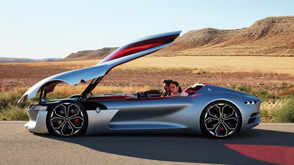 A couple sitting inside Renault TREZOR concept car with sliding roof door open