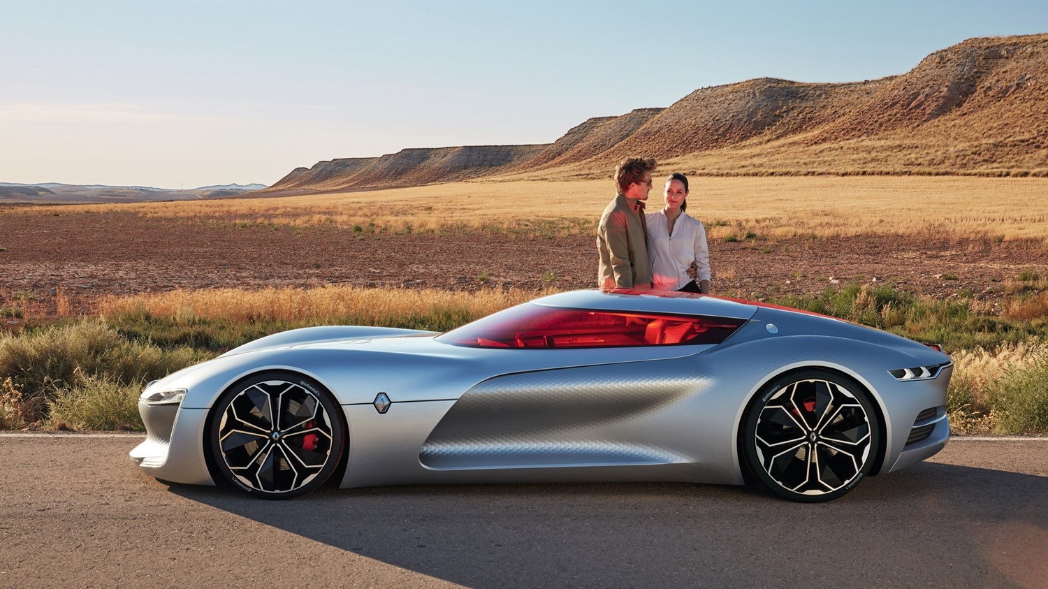A couple standing next to Renault TREZOR concept car on the road""